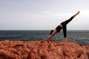 Young woman doing yoga flexibility on the rocks