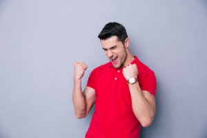Casual man celebrating success over gray background